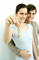 Young couple smiling at camera, woman holding up set of keys (thumbnail)