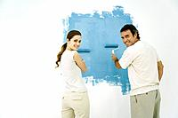 Couple painting wall blue using rollers, both looking over their shoulders and smiling at camera