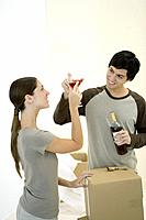 Couple clinking glasses of red wine, cardboard boxes nearby