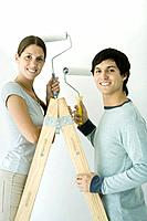 Couple standing on ladder, both holding up paint rollers and smiling at camera