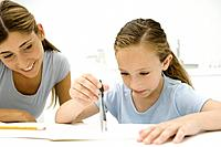Girl using compass to do geometry, mother watching and smiling