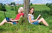 two teenage girls ouside using laptop and reading a book