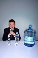 Businessman smiling at the camera with three water bottles on the table