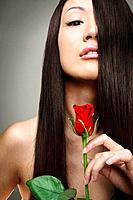Woman with long hair holding a red rose