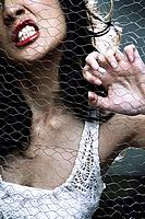 Woman pulling on wire mesh while clenching teeth