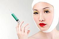 Woman with bandaged face holding a syringe (thumbnail)