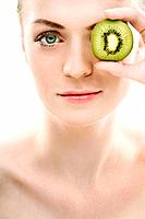Woman covering her eye with kiwi fruit (thumbnail)
