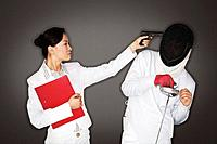 Businesswoman pointing a gun at man in fencing suit and mask (thumbnail)