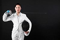 Businesswoman holding fencing mask and a fencing foil
