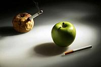 Rotten apple smoking cigarette, green apple with unlit cigarette by the side