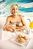 Woman reaching for fried yam puff with chopsticks (thumbnail)