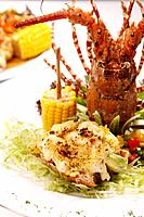 Main course of lobster, corn on cob and side salad