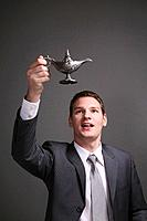Businessman holding up magic lamp