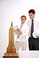 Model of Empire State Building, business people having discussion in the background