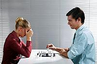 Businessman and businesswoman playing chess game
