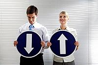 Businessman and businesswoman holding arrow signs showing different directions
