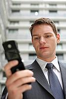Businessman text messaging on his cellphone