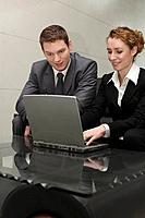 Businesswoman using laptop, businessman watching