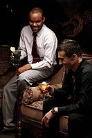 Businessmen sitting on antique sofa talking while having cocktails (thumbnail)