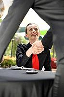 Businesswoman shaking hands with another business person (thumbnail)