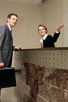 Receptionist showing direction to businessman