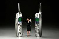 Businesswoman standing in between two ringing phones