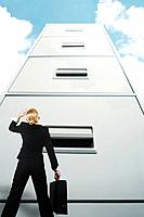Businesswoman looking up at a giant cabinet