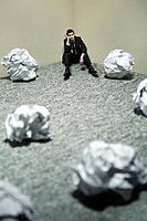 Businessman with giant sized crumpled papers on the floor