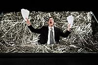 Businessman standing in a pile of paper clips, screaming while holding papers
