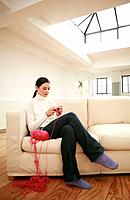 Woman sitting on couch knitting (thumbnail)