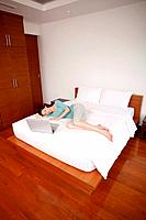 Woman lying in bed with her eyes closed, laptop beside her (thumbnail)