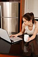 Woman holding cup while using laptop