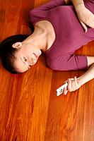 Woman lying on the floor text messaging on the cellphone
