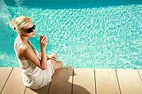 Woman sitting by the poolside holding a glass of juice