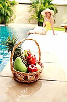 A basket of fruits with woman sitting by the poolside in the background