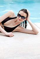 Woman with sunglasses posing by the poolside
