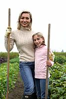 Mother and daughter posing with gardening tools in organic garden, Ladner, British Columbia, Canada