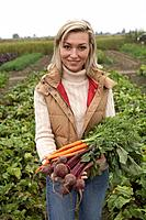 Woman with a bundle of fresh organic vegetables, Ladner, British Columbia, Canada