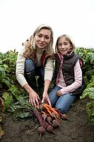 Mother and daughter at an organic farm with fresh vegetables, Ladner, British Columbia, Canada