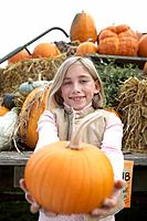 Girl holding organic pumpkin toward camera, Ladner, British Columbia, Canada