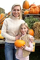 Mother with daughter holding organic pumpkin, Ladner, British Columbia, Canada