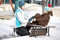13 year-old girl helps 9 year-old girl tie skates, at The Forks, Winnipeg, Canada