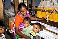 Woman working at a loom, children by her side, in a weaving factory, Madurai, Tamil Nadu, India Date: 15/05/2008 Ref: ZB362_115569_0071 COMPULSORY CRE...