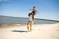 Man carries boy 7 on his shoulders as boy holds arms out, Grand Beach Provincial Park, Manitoba, Canada