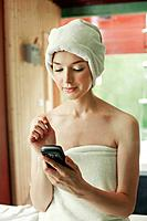 Woman in towel using PDA phone