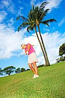Hawaii, Maui, Wailea Gold Golf Course, Female golfer swinging golf club.