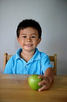Little boy holding green apple