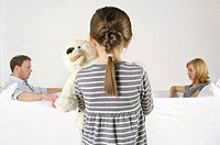 Frustrated couple sitting vis_a_vis, girl holding teddy bear standing in foreground