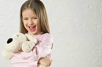 Girl holding a stuffed animal and laughing at camera