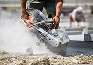 Construction worker using angle grinder
